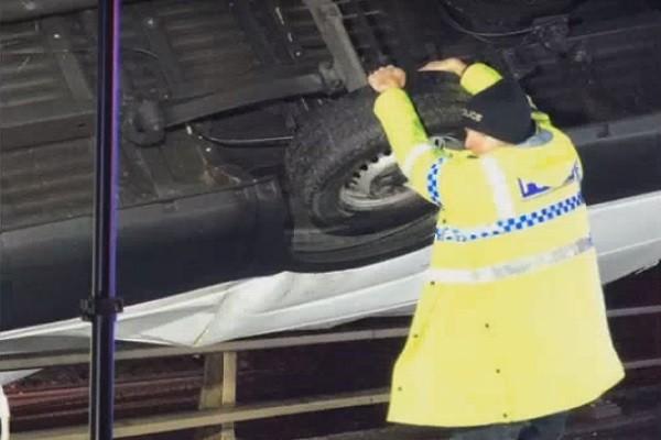 英汽車側翻掛橋邊 驚險搖擺 警員緊抓不放