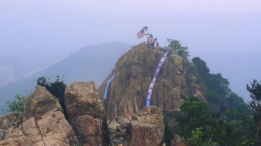 9月27日清晨,有港人在獅子山頂打出兩條巨型橫幅,上面寫有「中共亡黨滅國」「天滅中共」等字樣。(「香港自治行動」臉書圖片)
