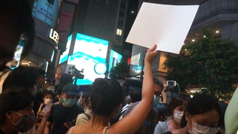港人反国安法游行 一少女高举白纸躲过港警追捕