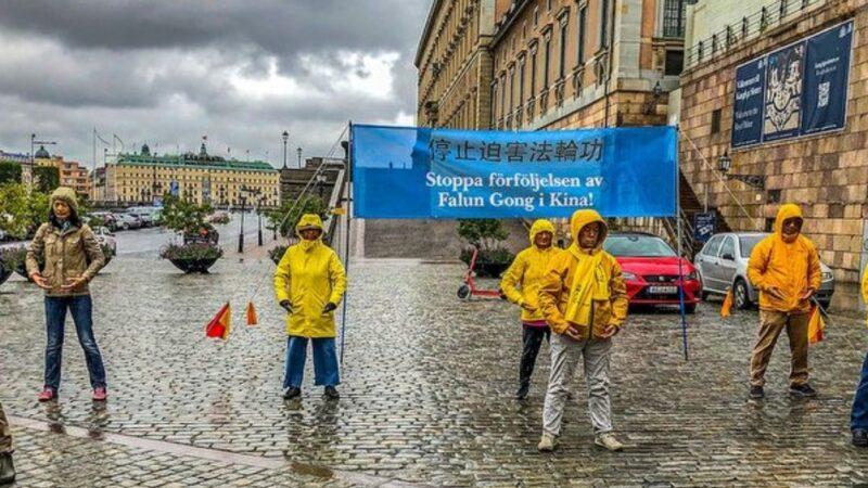 国会前 瑞典人冒雨围着法轮功学员听真相