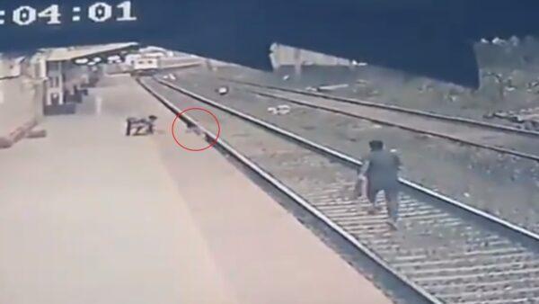火车就要撞上了! 他狂奔60米救回落轨男童