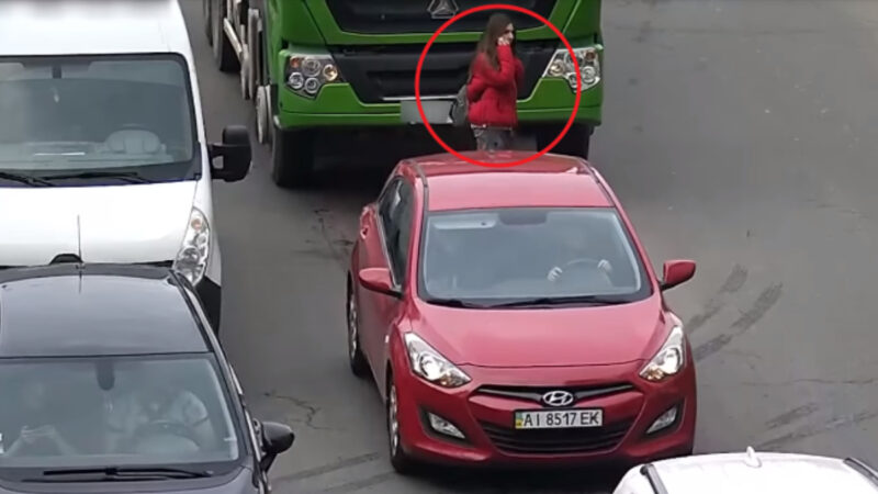 惊! 讲手机穿越车阵 年轻女子瞬间消失车底