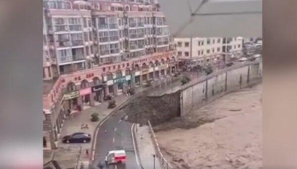 陝西暴雨,安康石泉縣一河邊道路出現大面積垮塌情況,樓房懸空。(視頻截圖)