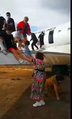 华夏航空涉事飞机在沙石地面上着陆,乘客们纷纷从舱门内跑出,现场没有扶梯,小朋友只能依靠家长才能下飞机。(视频截图)