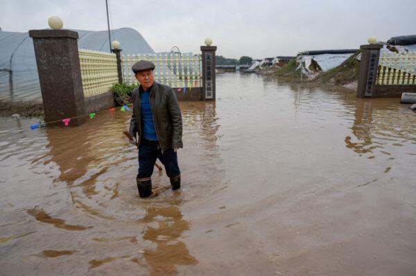 近期,山西省多地洪灾。图为晋中市洪灾现场,市民在洪水中行走。(STR/AFP via Getty Images)